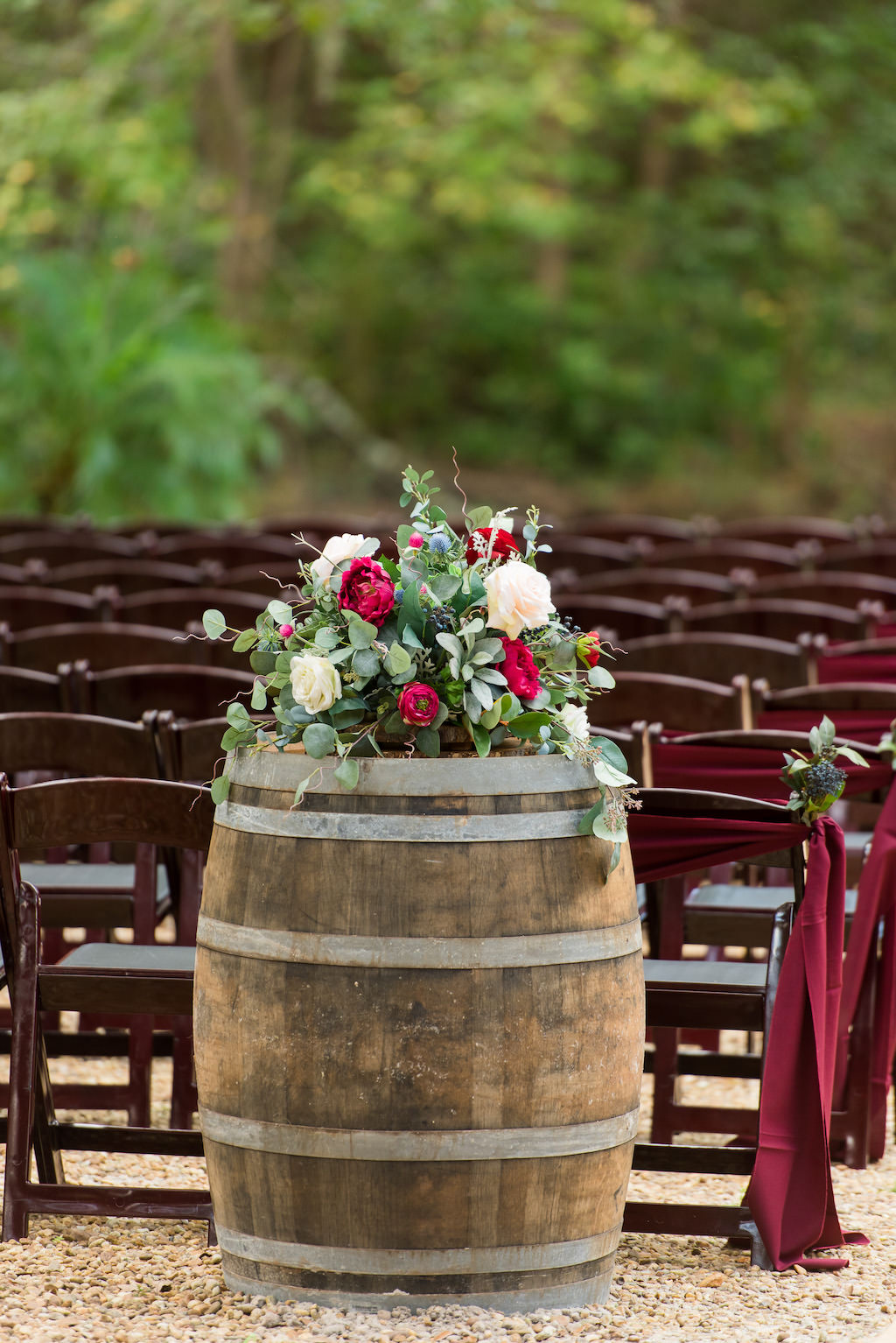 Rustic Outdoor Wedding Ceremony Decor, Wooden Barre with Greenery, Ivory, Burgundy Floral Bouquet, Wooden Folding Chairs and Burgundy Sashes