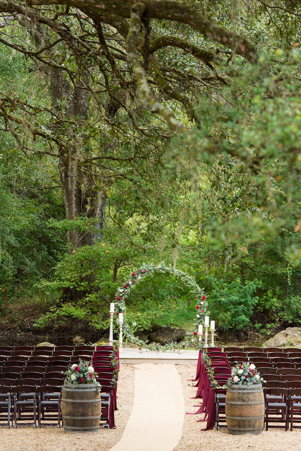 Rustic Outdoor Garden Wedding Ceremony, Wooden Chairs with Burgundy Sashes, Wooden Barrels with Floral Bouquets, Arch Covered in Greenery and Burgundy Flowers | Rustic Plant City Wedding Venue Kathleen's Garden
