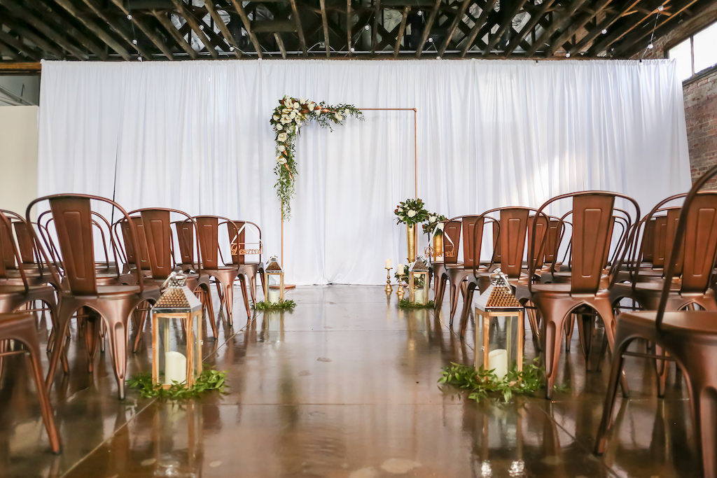 Industrial Inspired Wedding Ceremony, Bronze Metal Arch with White and Greenery Florals, Bronze Metal Chairs, Gold Lanterns with Greenery, White Draping | Tampa Bay Wedding Photographer Lifelong Photography Studios | Tampa Unique Industrial Wedding Venue CAVU | Wedding Rentals A Chair Affair