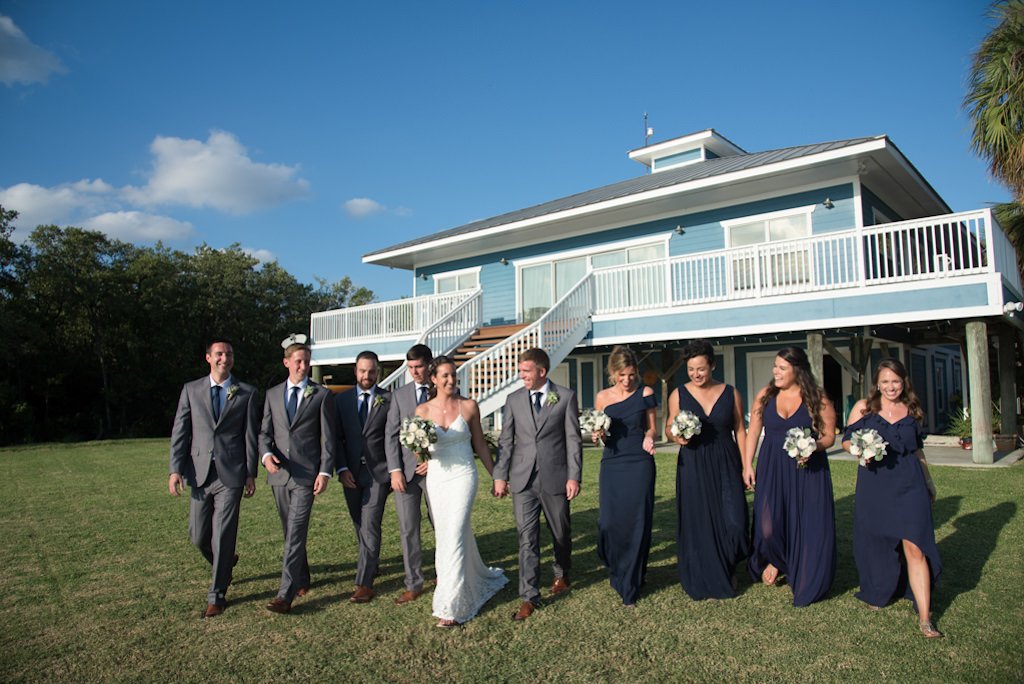 Florida Outdoor Bride, Groom and Wedding Party Portrait, Bridesmaids in Navy Blue Mismatched Style Long Dresses, Groomsmen in Grey Suits, Bride in Fitted Spaghetti Strap V Neckline Lace Wedding Dress | Waterfront Wedding Venue Tampa Bay Watch