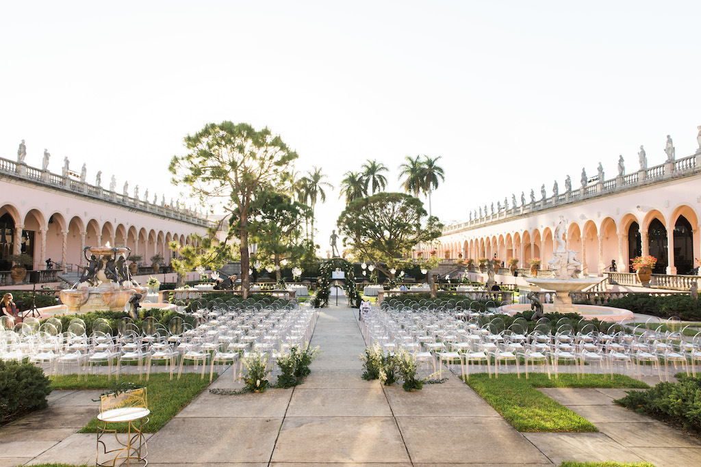 Elegant Modern Garden Courtyard Ceremony Decor, Ghost Chairs, Greenery and White Floral Ceremony Arch | Sarasota Wedding Venue Ringling Museum | Tampa Bay Wedding Planner NK Weddings