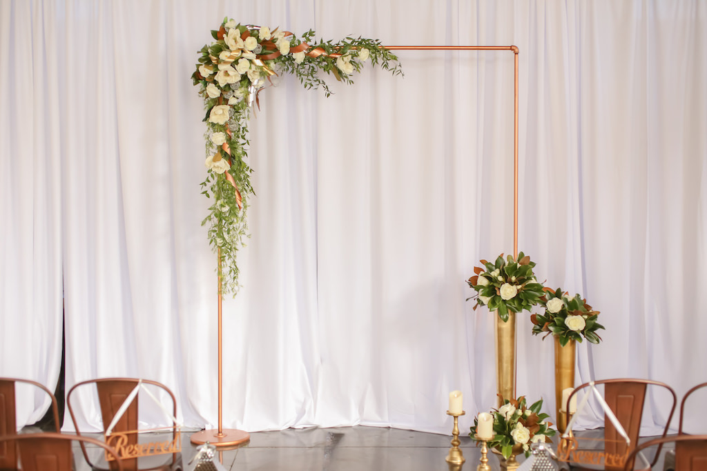Industrial Inspired Wedding Ceremony Decor, Bronze Metal Arch with White and Greenery Florals, Gold Metal Vases with Florals, White Draping   Tampa Bay Wedding Photographer Lifelong Photography Studios   Wedding Rentals A Chair Affair   Tampa Unique Industrial Wedding Venue CAVU