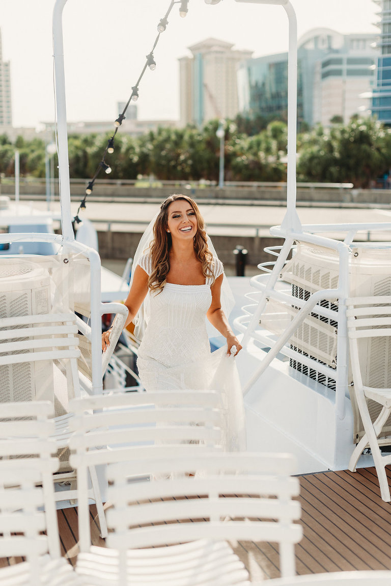 Florida Bride Climbing Stairs on Deck of Yacht in Scoop Neck Cap Sleeve Wedding Dress | Tampa Waterfront Wedding Venue Yacht Starship IV