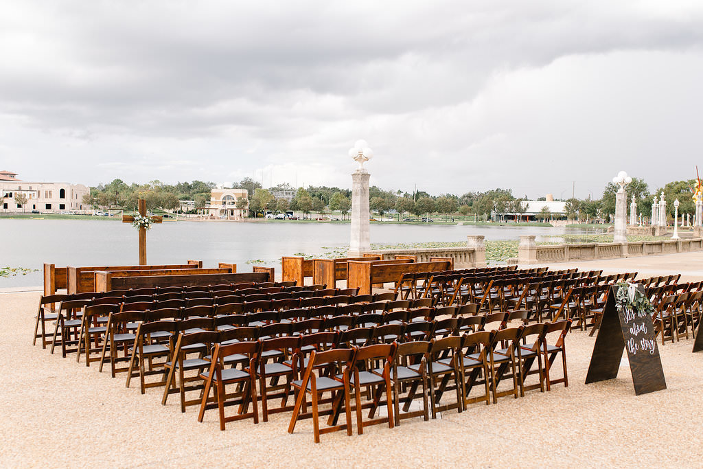 Tampa Bay Lakefront Wedding Ceremony Decor, Wooden Folding Chairs, Custom Folding Wooden Signs with Greenery Garland, Wooden Cross   Lakeland Wedding Venue Lake Mirror Amphitheater   Wedding Planner Love Lee Lane   Rentals A Chair Affair