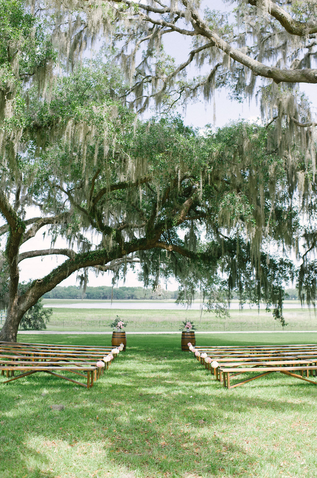Rustic Florida Outdoor Wedding Ceremony Decor, Wooden Benches, Wooden Barrels with Floral Arrangements | Inverness Rustic Wedding Venue Lakeside Ranch