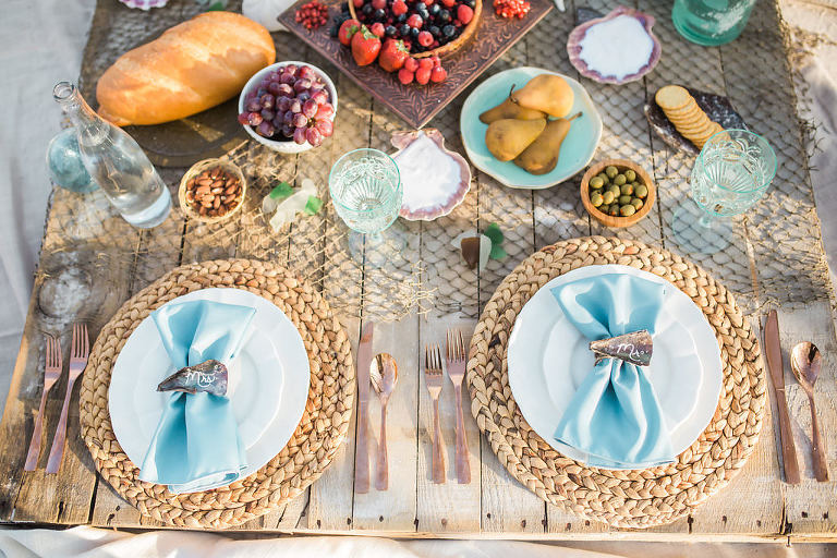 Florida Beach Inspired Wedding Styled Shoot, Natural Jute Braided Charger, White China Dishes, Light Blue Linens, Seashell Place Cards, Rose Gold Silverware, Fruit Platters and Aqua Crystal Glasses with Fishing Net Table Runner | Tampa Bay Wedding Planner UNIQUE Weddings and Events | Rentals Over the Top Linen Rentals