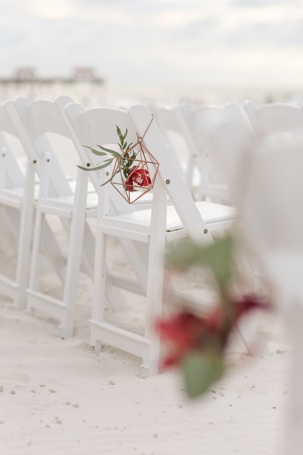 Florida Beach Wedding Ceremony Decor, White Folding Chairs with Geometric Vase and Red and Green Floral Inside | Tampa Bay Wedding Photographer Lifelong Photography Studios | Clearwater Beach Hotel Wedding Venue Hilton Clearwater Beach
