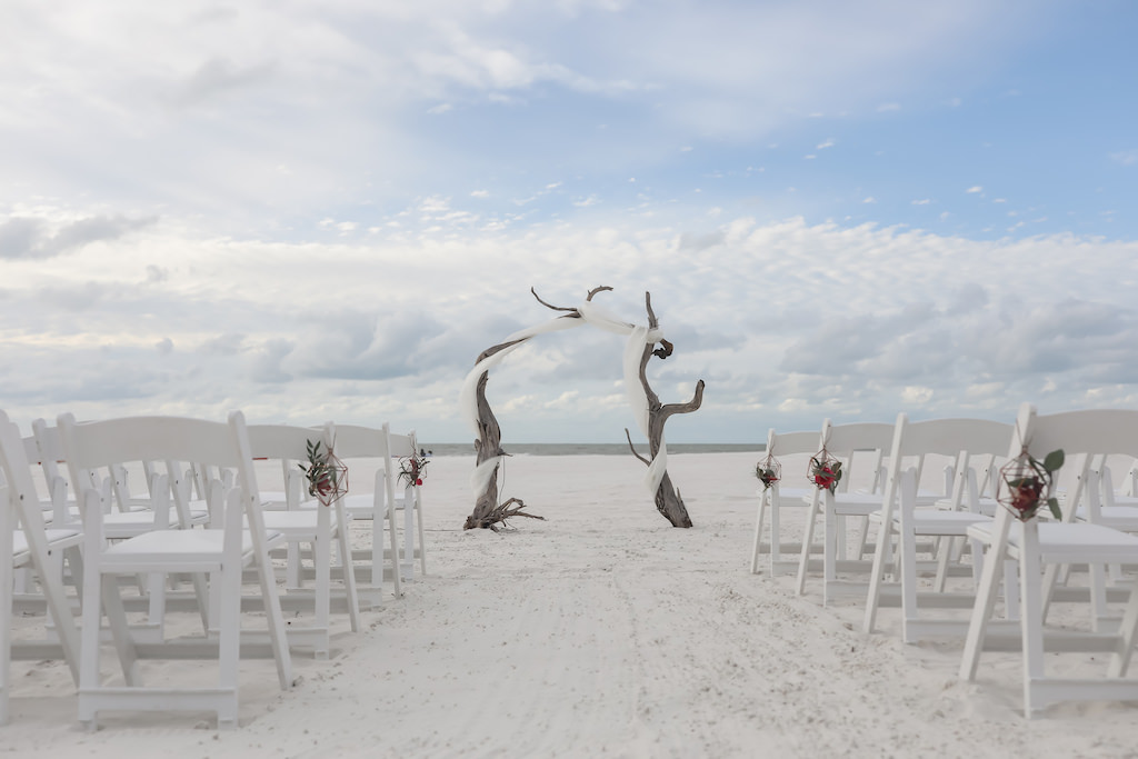 Florida Beachfront Wedding Ceremony Decor, White Folding Chairs with Geometric Vase and Red and Green Florals, Birchwood Arch with White Drapery | Tampa Bay Wedding Photographer Lifelong Photography Studios | Hotel Wedding Venue Hilton Clearwater Beach