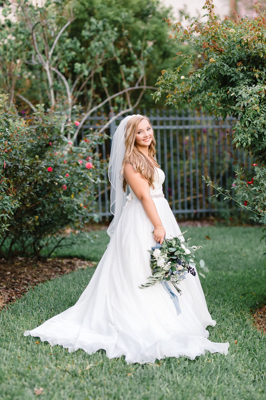Florida Bride Outdoor Wedding Portrait, Bride in Strapless Sweetheart Lace Bodice, Tulle and Organza Ball Gown Skirt with Rhinestone Belt and Wild Organic White, Blue, Silver Dollar Eucalyptus Floral Bouquet