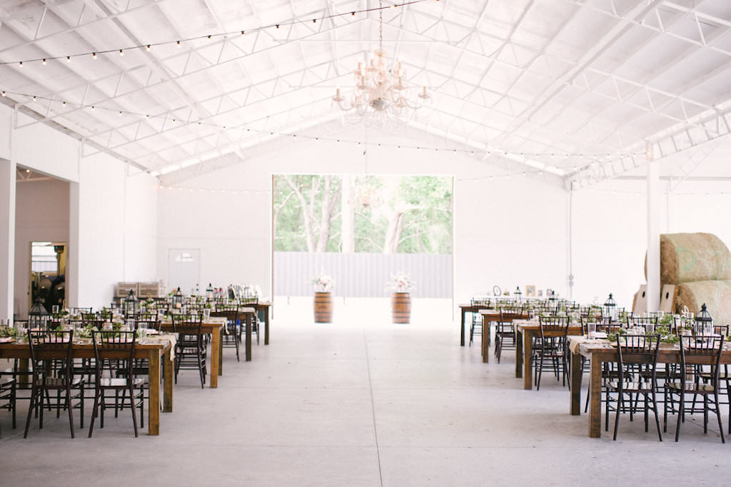 Florida Rustic Wedding Reception Decor, Long Wooden Tables, Black Chiavari Chairs, Wooden Barrels with Floral Arrangements, Hanging Bistro Lights | Inverness Wedding Venue Lakeside Ranch