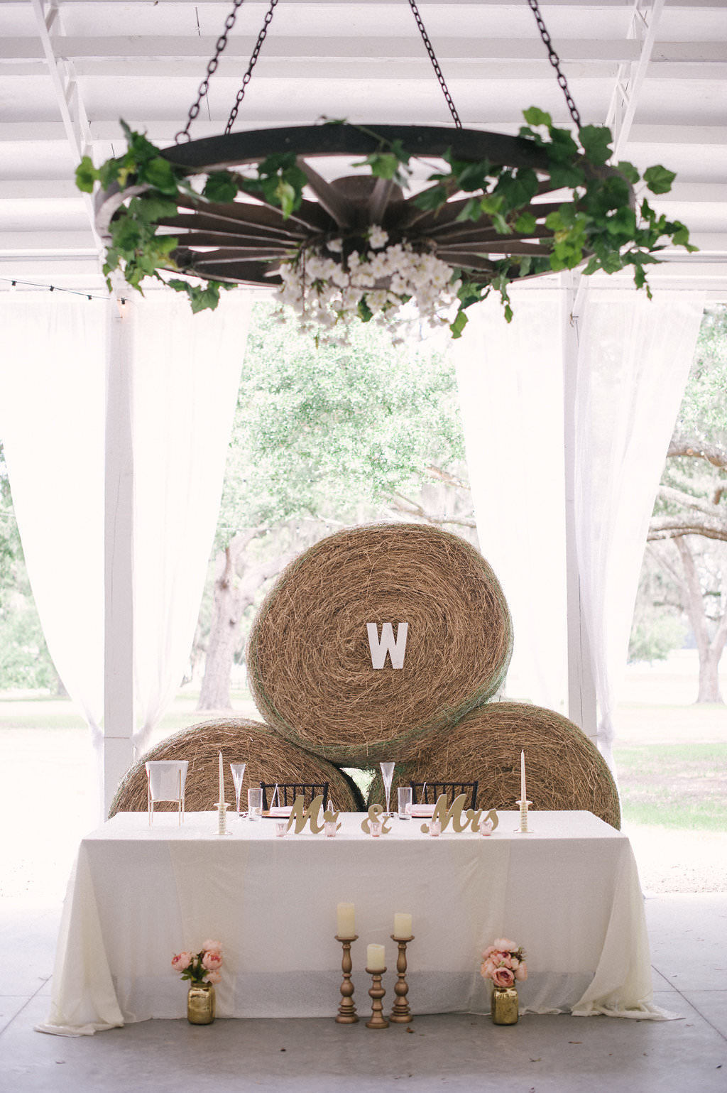 Tampa Bay Rustic Wedding Reception Decor, Sweetheart Table with White Tablecloth, Gold Candlesticks, Blush Pink Floral Arrangements in Gold Vases, Gold Mr and Mrs Signs, Hay Barrels Backdrop, Wooden Wheel Chandelier Decorated with Greenery and White Florals