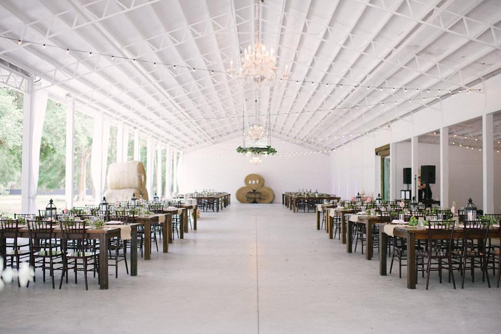 Florida Rustic Wedding Reception Decor, Long Wooden Tables with Black Chiavari Chairs, Hay Barrels, Hanging Bistro Lights | Tampa Bay Wedding Venue Lakeside Ranch