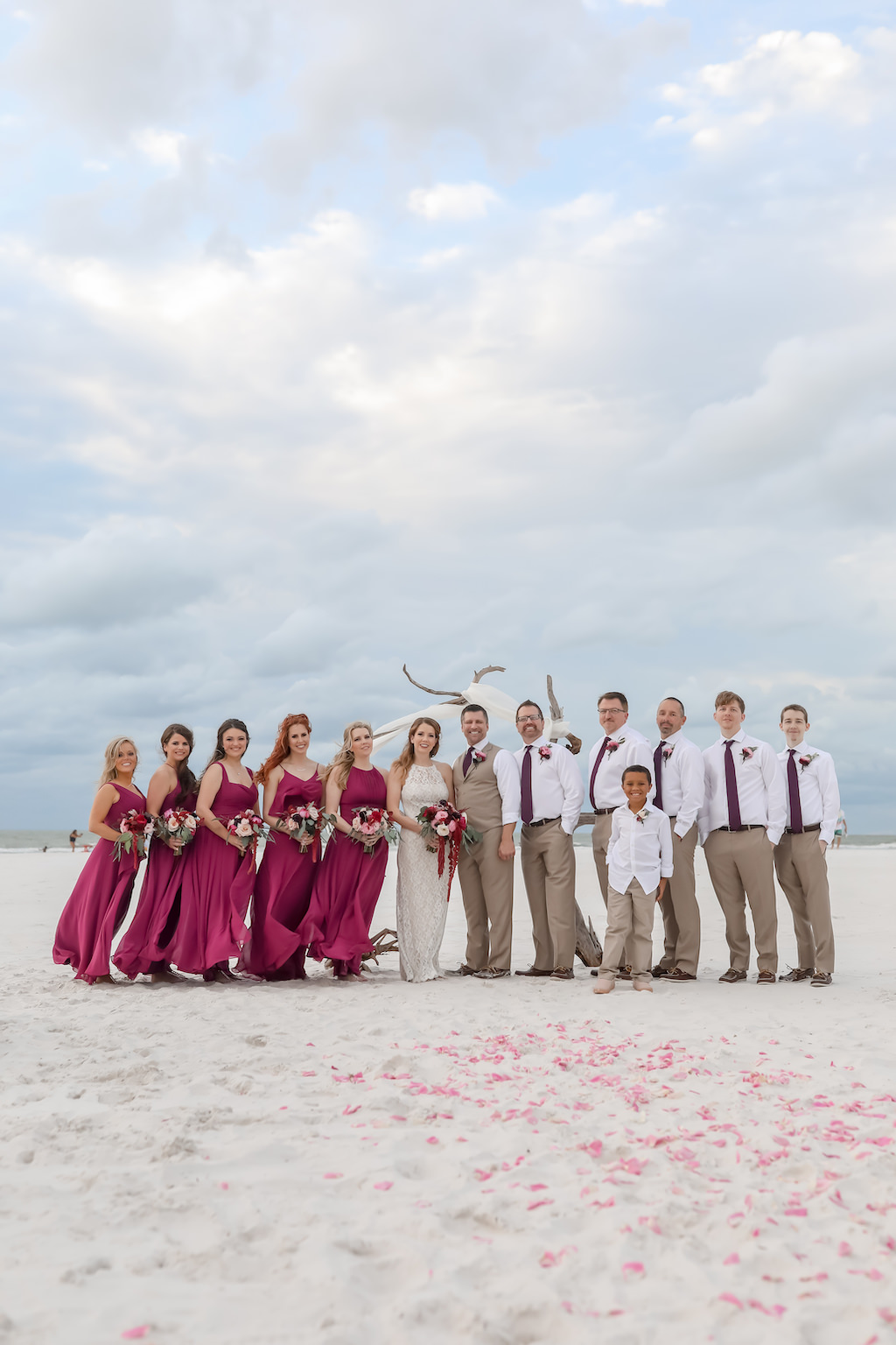 Florida Beachfront Bride, Groom and Bridal Party Wedding Portrait, Bridesmaids in Pinkish Purple Magenta Long Mismatched Style Dresses, Bride in Long Fitted Lace Halter Strap BHLDN Wedding Dress, Groom and Groomsmen in Khaki Suit Pants, White Shirts and Plum Purple Ties | Tampa Bay Wedding Photographer Lifelong Photography Studios | Clearwater Beach Hotel Wedding Venue Hilton Clearwater Beach