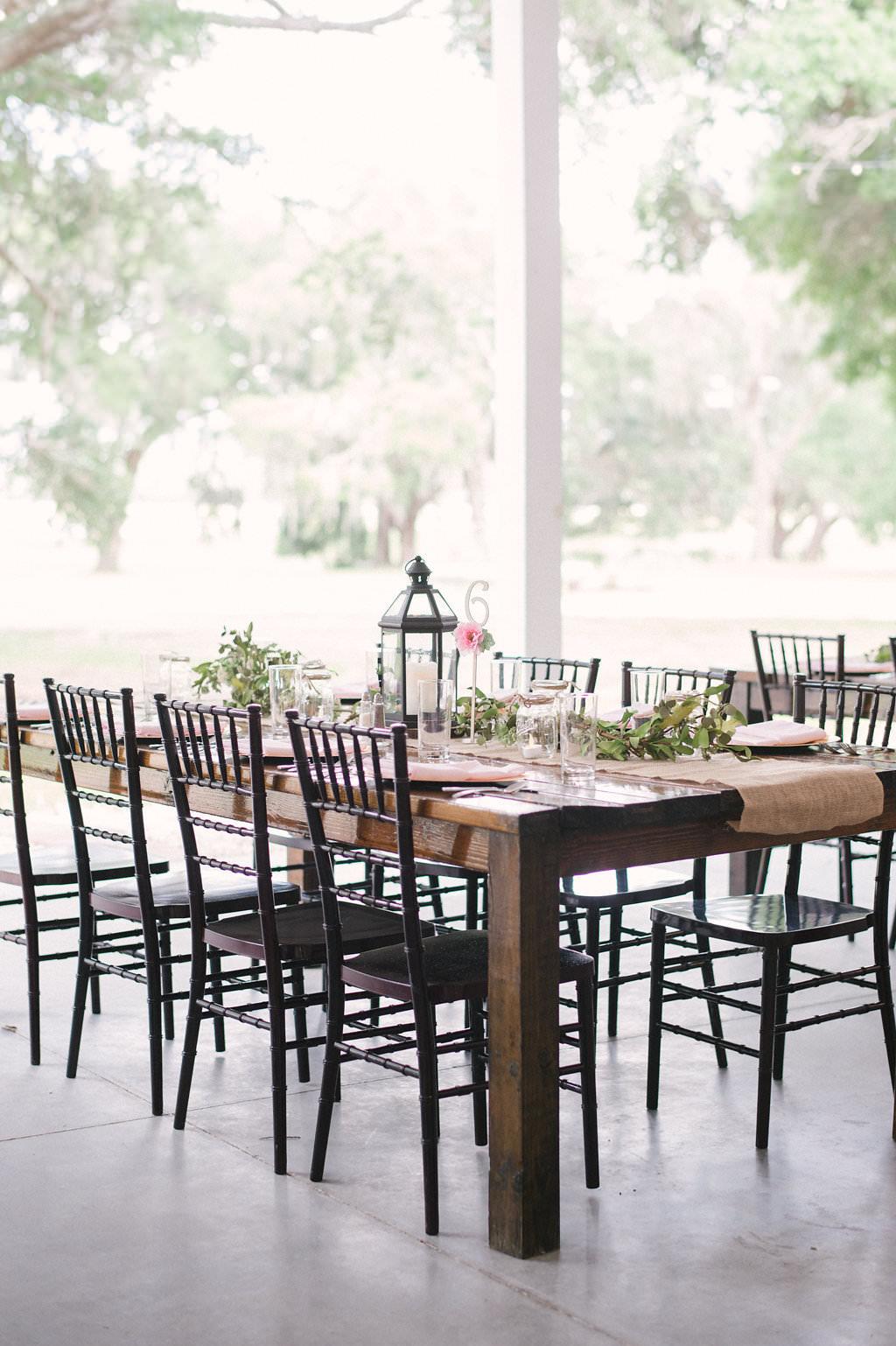 Tampa Bay Rustic Wedding Reception Decor, Long Wooden Table with Black Chiavari Chairs, Burlap Table Runner, Black Lantern and Greenery Garland