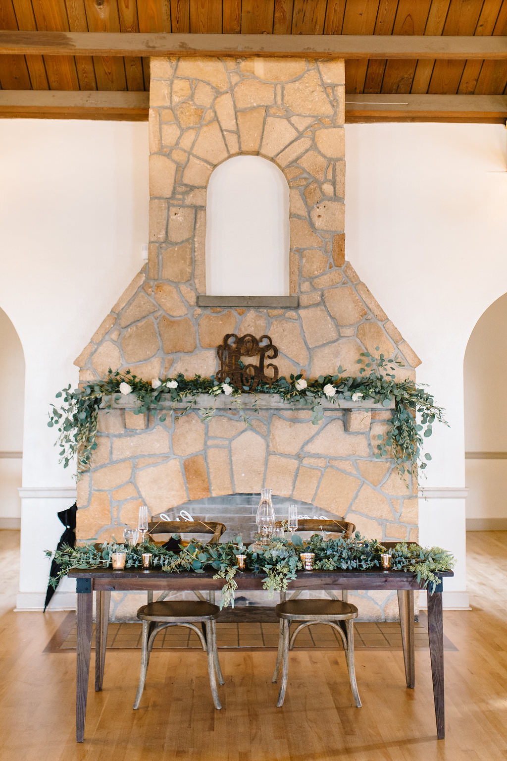 Vintage Rustic Whimsical Inspired Wedding Reception Decor, Wooden Table with Wooden Chiavari Chairs, Greenery Garland Sweetheart Table, Brick Fireplace Backdrop with Greenery Garland and White Florals   Tampa Bay Wedding Planner Love Lee Lane   Lakeland Wedding Venue Magnolia Building