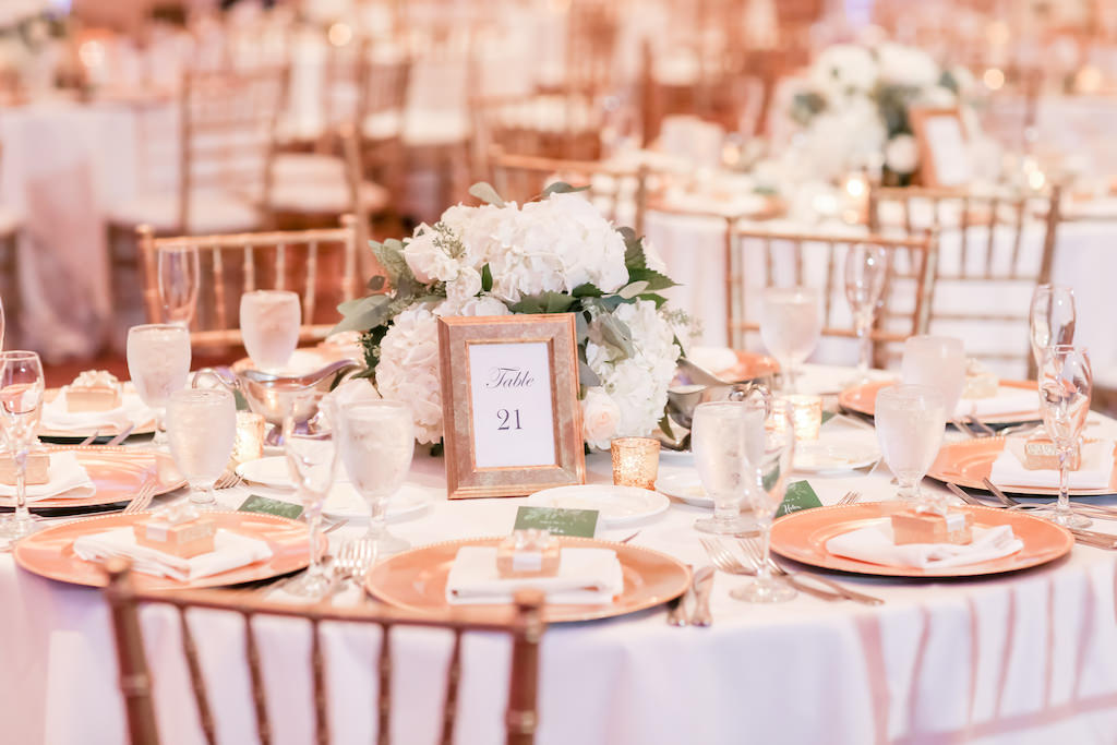 Wedding Reception Decor Round Table With White Tablecloth Gold Chiavari Chairs Gold Chargers Gold Frame With Table Number Low White Hydrangeas And Greenery Floral Centerpiece Tampa Bay Wedding Photographer Lifelong Photography