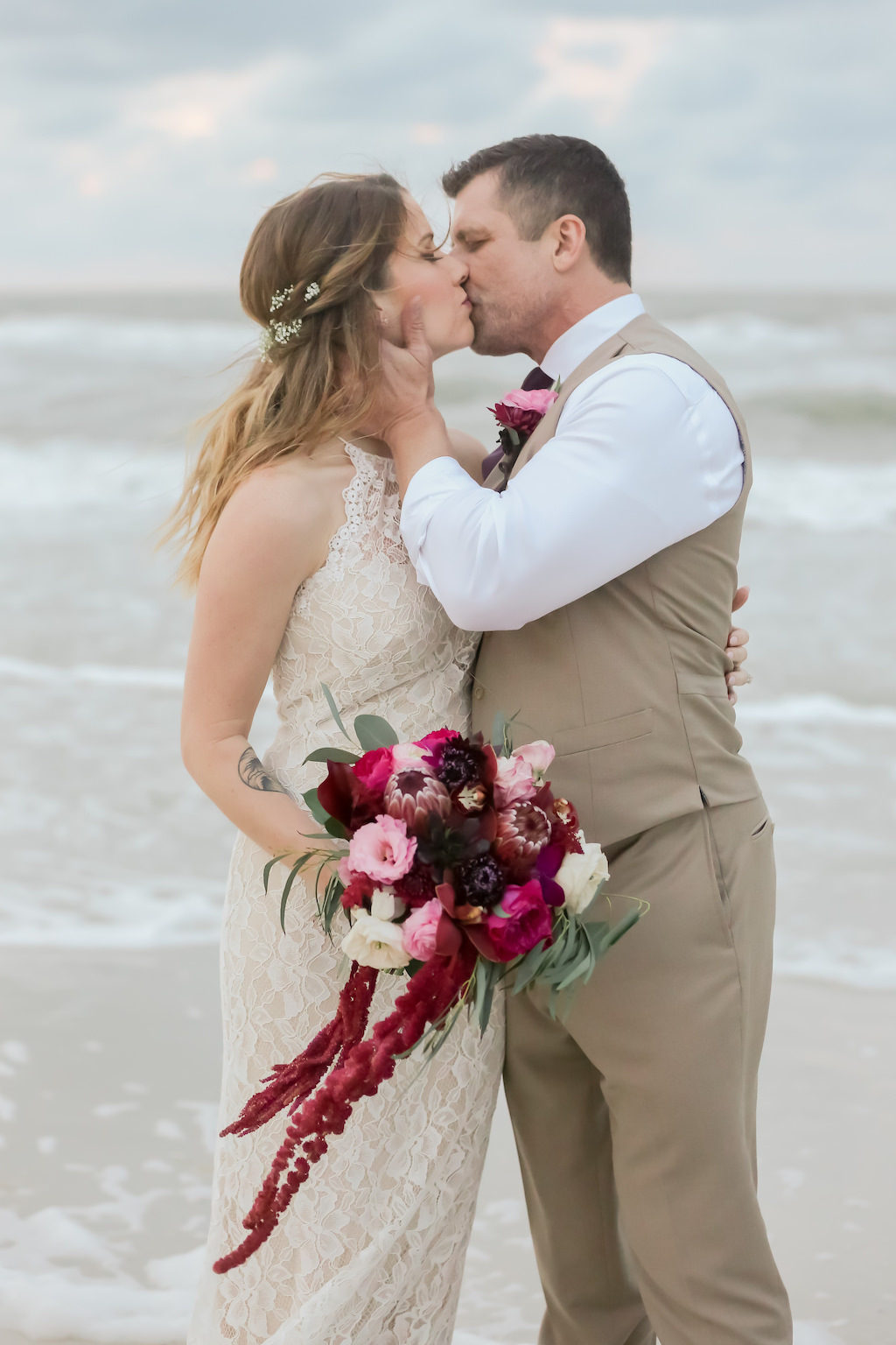 Florida Bride and Groom Sunset Wedding Portrait on the Beach, Bride in Long Fitted Lace Halter Strap BHLDN Wedding Dress with Jewel Tone, Purple, Pink, Plum, White and Greenery Organic Floral Bouquet, Groom in Khaki Suit and Vest | Tampa Bay Wedding Photographer Lifelong Photography Studios | Clearwater Beach Hotel WEdding Venue Hilton Clearwater Beach | Hair and Makeup Artist Femme Akoi