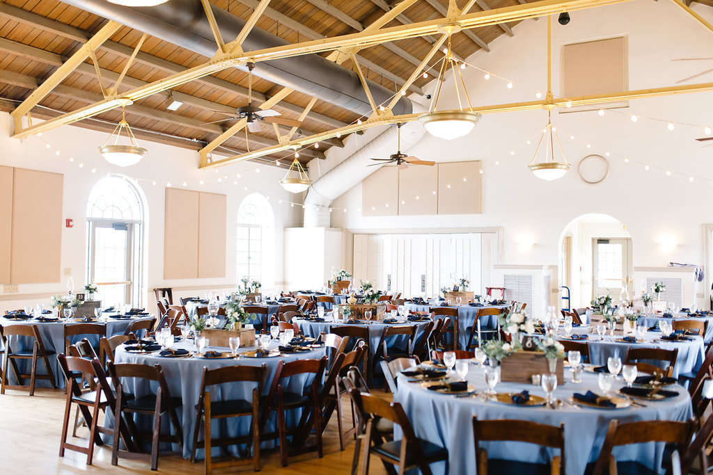 Vintage Rustic Whimsical Inspired Wedding Reception Decor, Round Tables with Dusty Blue Tablecloths, Wooden Chiavari Chairs, Low Centerpieces, Hanging Lights   Tampa Bay Wedding Planner Love Lee Lane   Lakeland Wedding Venue Magnolia Building   Rentals A Chair Affair