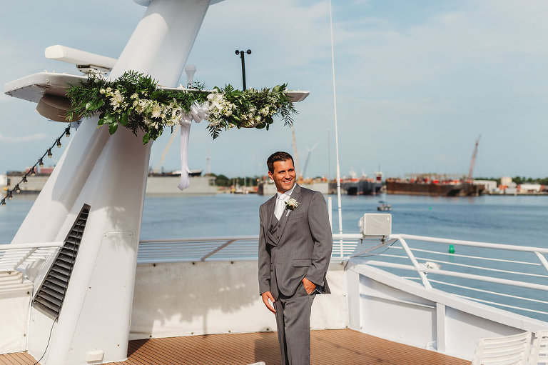 Florida Groom Waiting for Bride on Deck of Yacht in Grey Suit | Tampa Waterfront Wedding Venue Yacht Starship IV