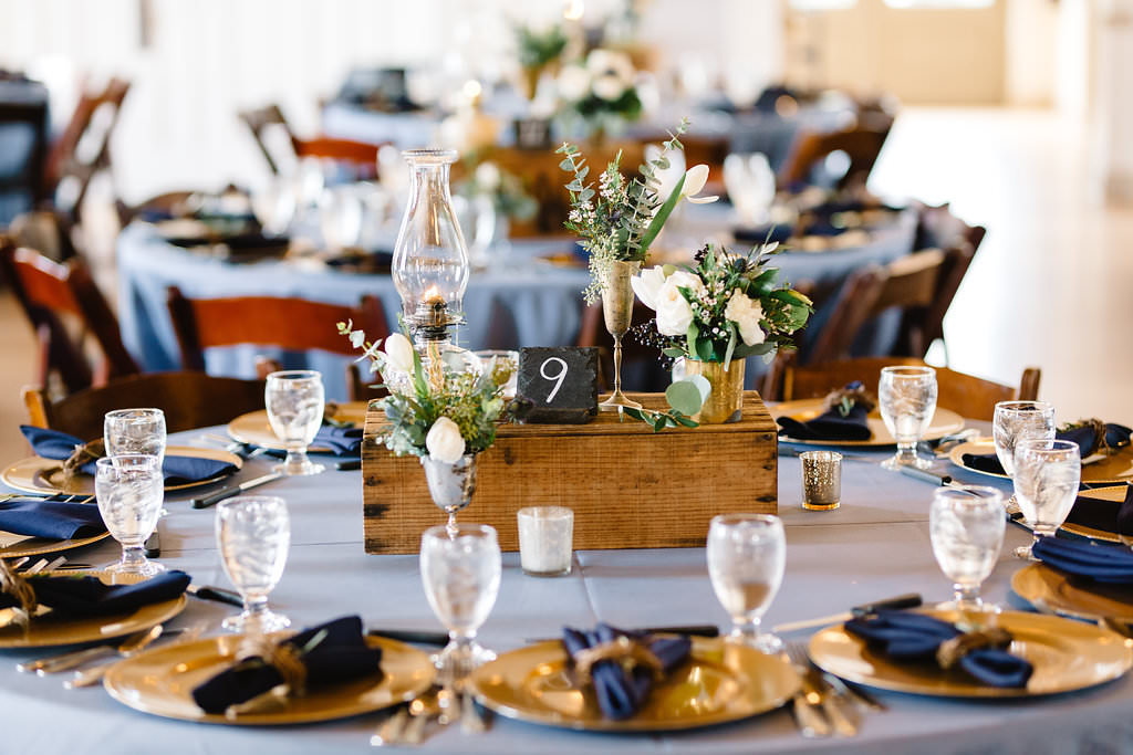Vintage Rustic Whimsical Inspired Wedding Reception Decor, Round Table with Dusty Blue Tablecloth, Gold Chargers, Navy Blue Linens, Wooden Pallet Box with Candelsticks, Vases with Greenery and White Floral Centerpieces   Tampa Bay Wedding Planner Love Lee Lane   Rentals A Chair Affair