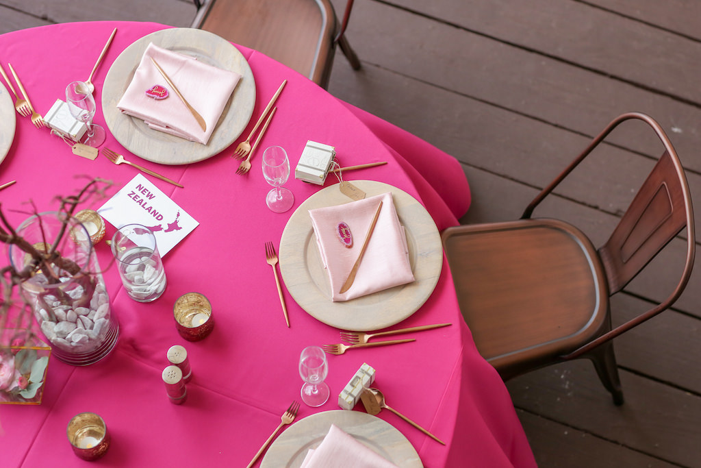 Travel Inspired Wedding Reception Decor, Round Table with Hot Pink Tablecloth, Wooden Chargers, Bronze Metal Chairs, Blush Pink Linens, Rose Gold Silverware, Glass Vase with Wooden Sticks Centerpieces | Tampa Bay Wedding Photographer Lifelong Photography Studios