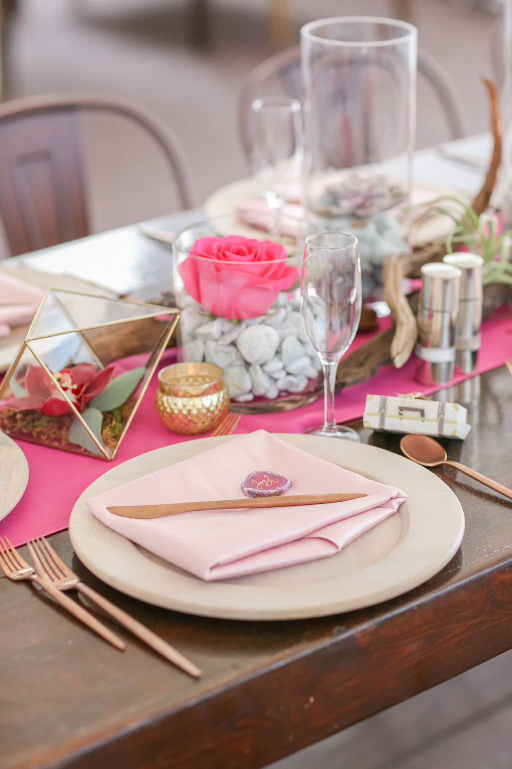 Travel Inspired Wedding Reception Decor, Long Wodoen Feasting Table, Wooden Chargers with Blush Pink Linens, Hot Pink Table Runner, Birchwood and Glass Vase with Stone and Pink Rose Centerpieces, Geometric Vase with Dark Pink Floral | Tampa Bay Wedding Photographer Lifelong Photography Studios