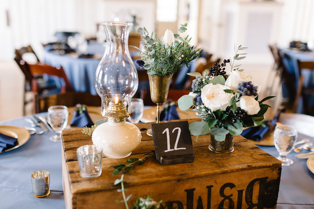 Vintage Rustic Whimsical Inspired Wedding Reception Decor, Round Table with Dusty Blue Tablecloth, Gold Chargers, Navy Blue Linens, Wooden Pallet Box with Candelsticks, Vases with Greenery and White Floral Centerpieces   Tampa Bay Wedding Planner Love Lee Lane