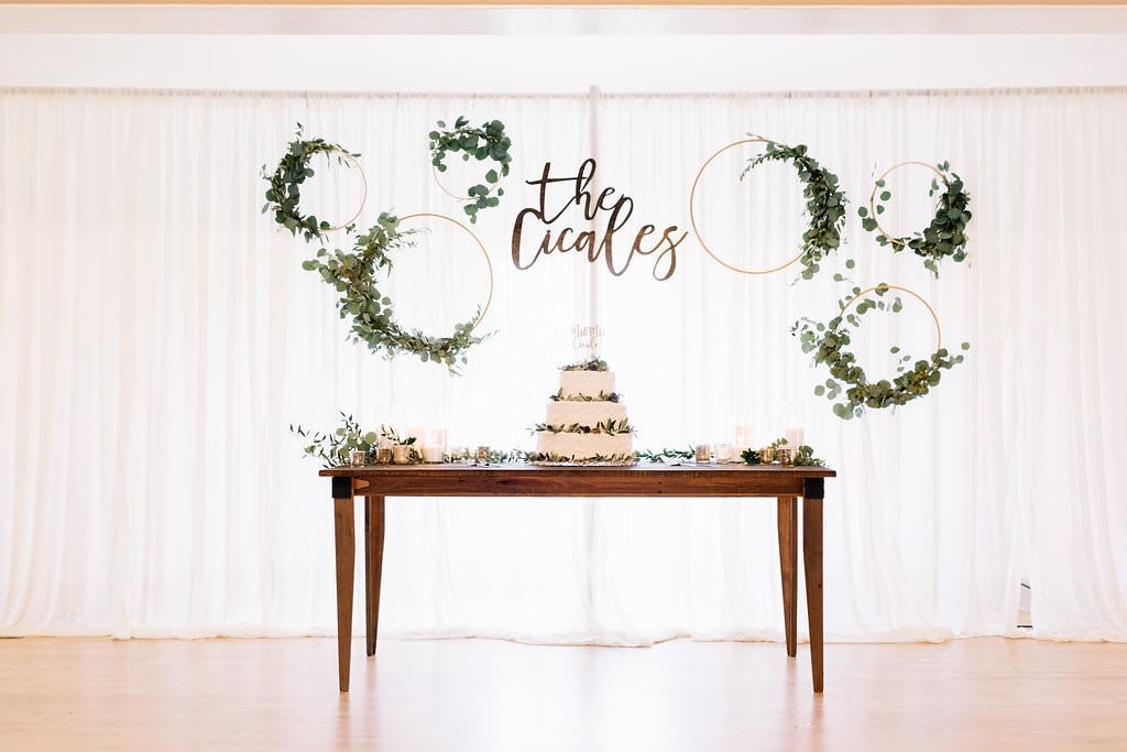 Vintage Rustic Whimsical Wedding Reception Decor, Long Wooden Dessert Table with Three Tier White Wedding Cake with Greenery, White Drapery Backdrop with Gold Circular Hoops Decorated with Greenery Garland | Tampa Bay Wedding Planner Love Lee Lane