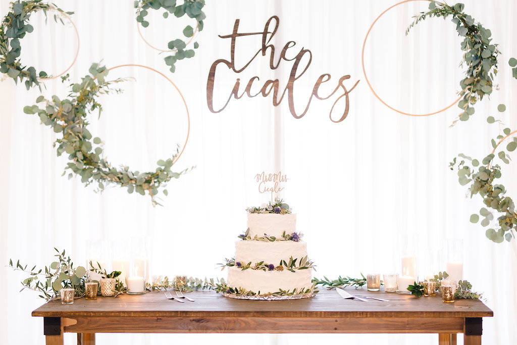 Vintage Rustic Whimsical Wedding Reception Decor, Long Wooden Table with Three Tier White Wedding Cake with Real Greenery Decor, Custom Cake Topper, White Drapery Backdrop with Gold Circular Hoops Decorated with Greenery Garland and Custom Laser Cut Sign   Tampa Bay Wedding Planner Love Lee Lane