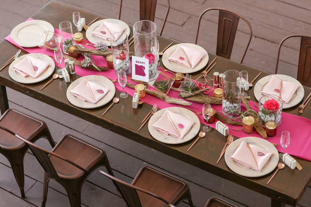 Travel Inspired Wedding Reception Decor, Long Wooden Feasting Table, Bronze Metal Chairs, Hot Pink Table Runner, Wooden Chargers with Blush Pink Linens, Birchwood, Glass Vases with Stones, Succulents and Florals Centerpieces | Tampa Bay Wedding Photographer Lifelong Photography Studios