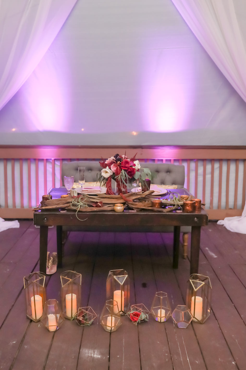 Travel Inspired Wedding Reception Decor, Wooden Sweetheart Table with Birchwood and Jewel Tone Purple, Pink, Plum, White and Greenery Floral Bouquet, Geometric Vases with Candles and Purple Uplighting | Tampa Bay Wedding Photographer Lifelong Photography Studios | Clearwater Beach Hotel Wedding Venue Hilton Clearwater Beach