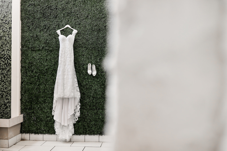 Fitted Lace Sweetheart Neckline with Thick Lace Straps Hanging on Greenery Wall | Tampa Bay Wedding Photographer Lifelong Photography Studios | Downtown St. Pete Wedding Venue The Birchwood