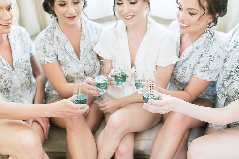 Florida Bride and Bridesmaids Getting Ready Wedding Portrait in Dusty Blue Floral Short Sleeve and Shorts Pajamas with Personalized Champagne Glasses | Tampa Bay Hair and Makeup Artist Michele Renee the Studio