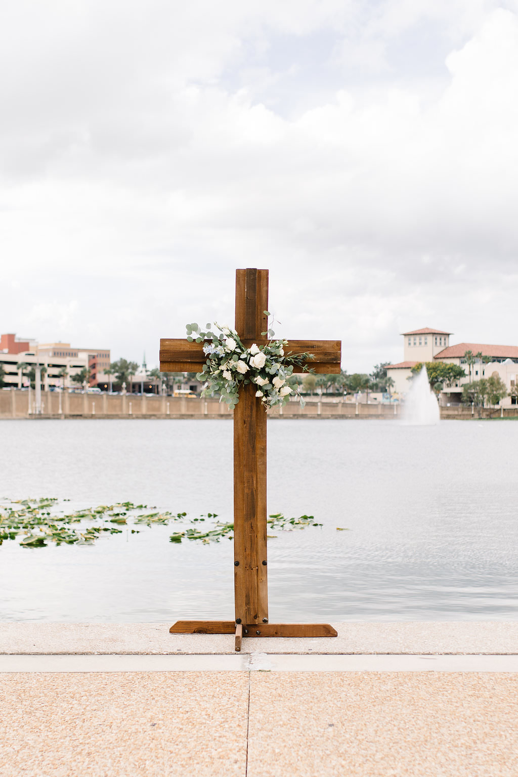 Tampa Bay Lakefront Wedding Ceremony Decor, Wooden Cross with Greenery and White Florals   Lakeland Wedding Venue Lake Mirror Amphitheatre   Wedding Planner Love Lee Lane