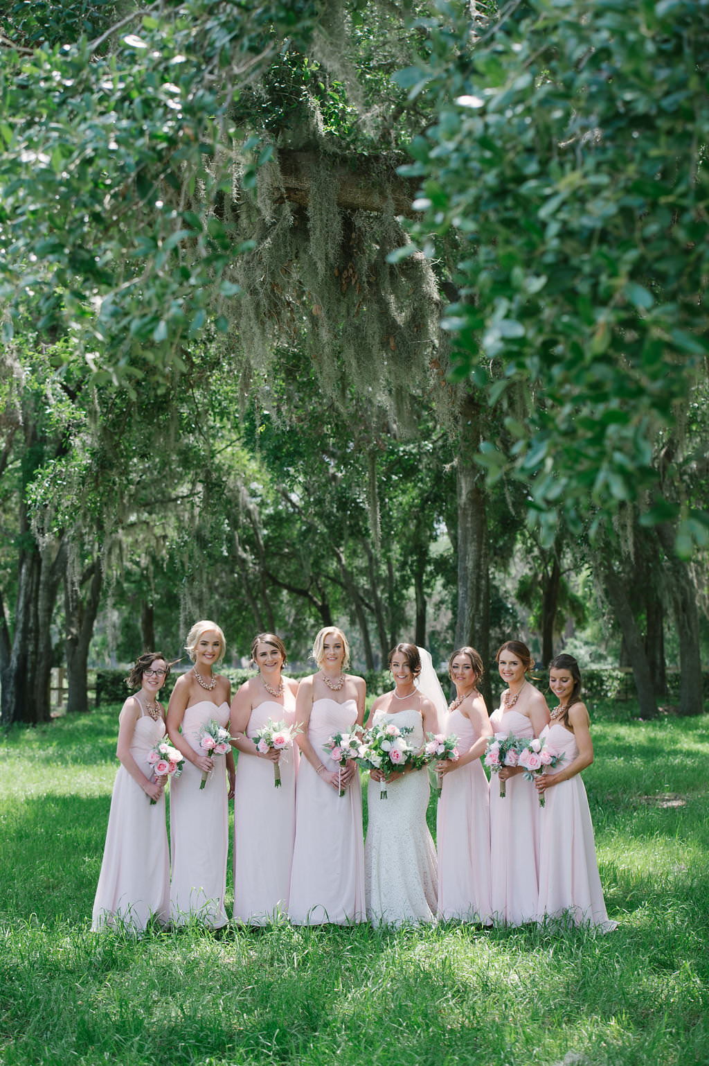 Florida Bride and Bridesmaids Outdoor Wedding Portrait, Bridesmaids in Blush Pink Long Matching Dresses, Bride in Lace Strapless Sweetheart Fitted Wedding Dress | Inverness Rustic Wedding Venue Lakeside Ranch
