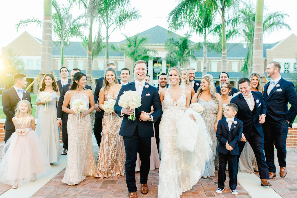 Florida Bride, Groom and Wedding Party Outdoor Portrait, Bride in Low V Neckline with Straps Lace Wedding Dress, Groom in Navy Blue Tuxedo and Blush Pink Bowtie Holding Brides Ivory Floral Bouquet