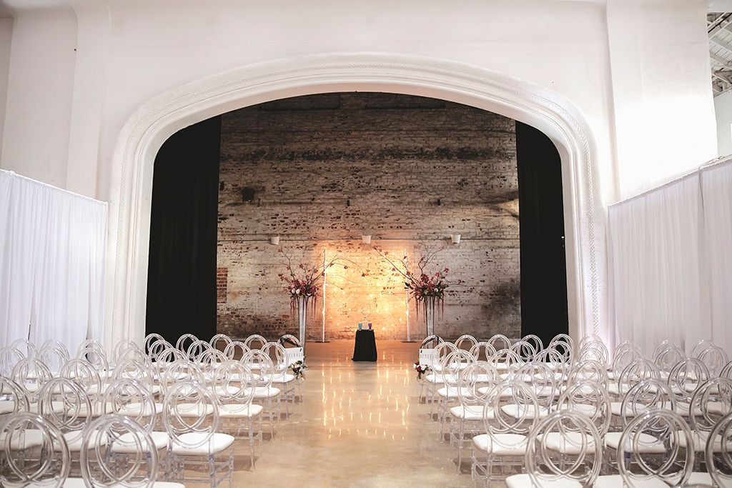 Modern Wedding Ceremony Decor, Clear Ghost Chairs with White Cushions, Tall Pedestals with Floral Arrangements | Tampa Bay Wedding Venue Rialto Theatre | Wedding Planner Kelly Kennedy Wedding and Events
