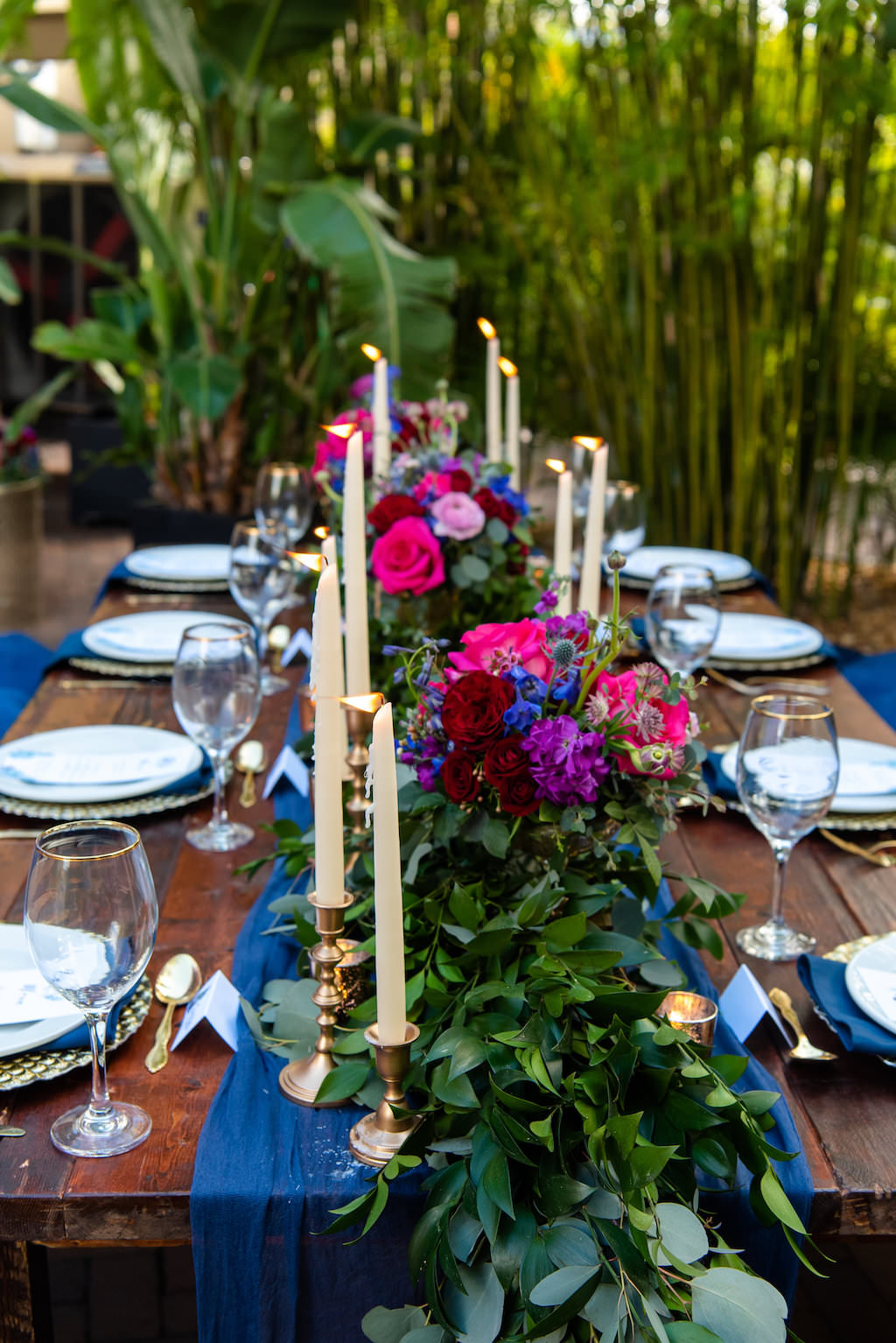 Wedding Reception Decor, Long Wooden Table with Velvet Blue Pillows, Blue Table Runner and Linens, Pale Blue Plates, Gold Silverware, Small and Tall Gold Candlesticks, Greenery Garland, Pink, Blue, and Red Low Floral Centerpieces, Bamboo Garden Backdrop | St. Pete Wedding Venue NOVA 535 | Tampa Bay Wedding Photographer Caroline and Evan Photography | Florist Monarch Events and Design | Designer and Planner Southern Weddings and Events | Rentals A Chair Affair