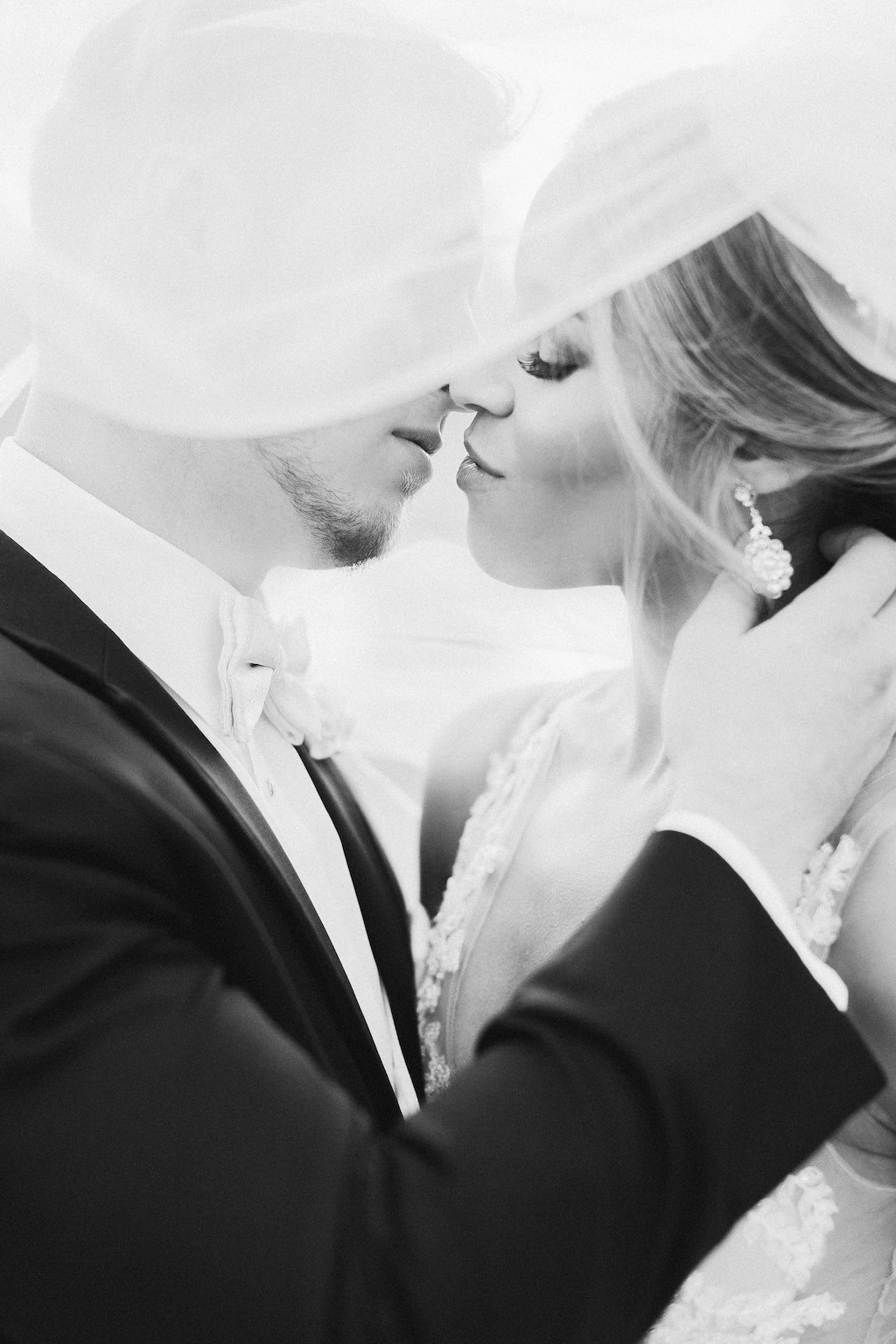 Creative Black and White Bride and Groom Wedding Portrait with Veil Blowing in Wind