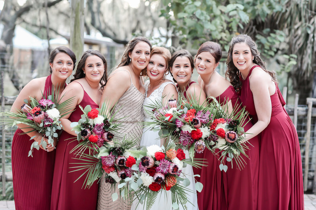 Bride and Bridesmaids Outdoor Wedding Portrait, Bridesmaids in Mismatched Style Red Long Dresses, Maid of Honor in Rhinestone and Champagne Dress Holding Tropical Orange, Red, Purple, Pink, White, Silver Dollar Eucalyptus and Greenery Floral Bouquets | Tampa Bay Wedding Photographer Lifelong Photography Studio | Hair and Makeup Michele Renee the Studio