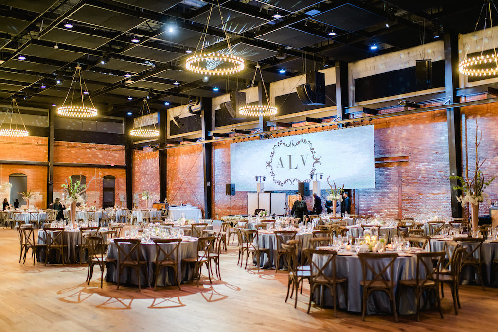 Wedding Reception Deco, Round Tables with Dusty Blue Tablecloths, Wooden Chiavari Chairs, Projector Screen with Monogram Initials | Historic Industrial Downtown Tampa Wedding Venue Armature Works