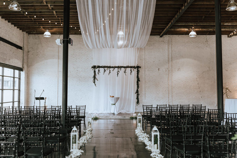 Romantic Wedding Ceremony Decor, White Drapery, Greenery Garland Arch, White Lanterns and White Flower Petals Down Ceremony Aisle | Lakeland Industrial Wedding Venue HAUS 820