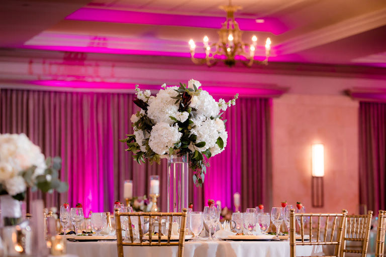 Hotel Ballroom Classic Wedding Reception Decor, Pink Uplighting, Round Tables with Gold Chiavari Chairs, White Tablecloth, Tall Glass Cylinder Vase with White and Greenery Floral Centerpiece | Wedding Planner Special Moments Event Planning | Rentals Gabro Event Services | Tampa Marriott Water Street