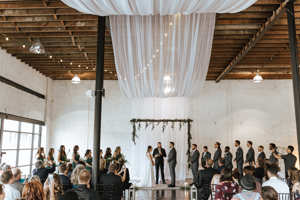 Romantic Wedding Ceremony Decor, Bride and Groom Exchanging Vows Under Greenery Arch and White Draping Wedding Portrait | Lakeland Industrial Wedding Venue HAUS 820