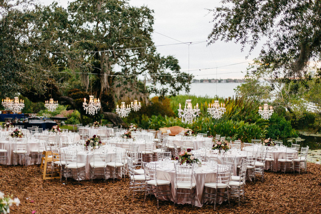 Outdoor Garden Wedding Reception Decor, Round Tables, Ghost Acrylic Chiavari Chairs, Low Flower Centerpieces, Hanging Crystal Chandeliers   Sarasota Wedding Venue Marie Selby Botanical Gardens   Tampa Bay Wedding Planner NK Productions