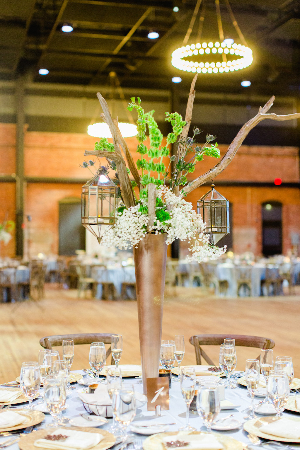 Nature Inspired Wedding Reception Decor, Tall Bronze Vase with Wooden Branches, Greenery, White Baby's Breath and Hanging Lanterns Centerpiece