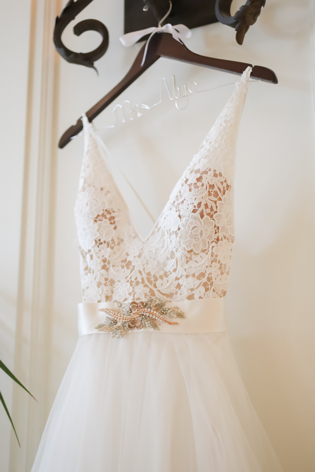 Lace Nude and White Deep V Neckline with Straps, Ivory Sash and Floral Rhinestone Brooch, Tulle and Illusion Skirt on Custom Wooden Hanger   Tampa Bay Wedding Photographer Lifelong Photography Studios