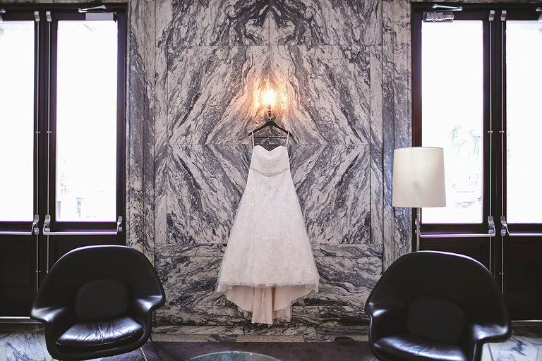Strapless Lace Ballgown Wedding Dress with Rhinestone Belt Hanging in Front of Black and White Marble Wall