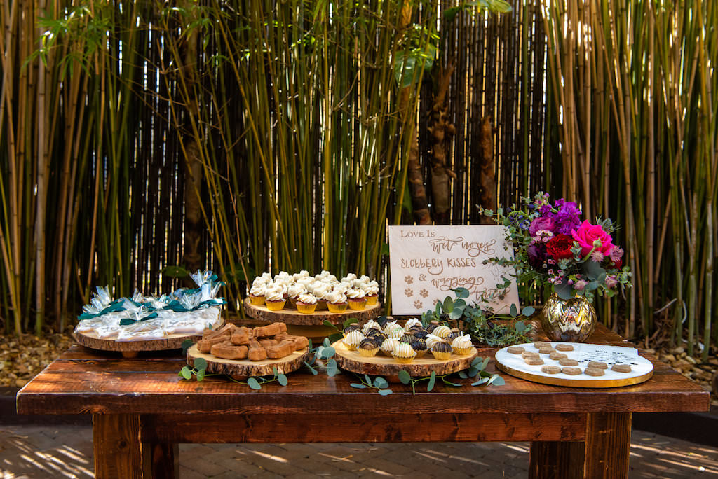 Bamboo Garden Wedding Reception Dessert Table, Rustic Wooden Serving Platters with Cupcakes and Cookies, Custom Wooden Sign, Gold Vase with Pink, Purple and Greenery Floral Centerpiece | Tampa Bay Wedding Photographer Caroline and Evan Photography | Designer and Planner Southern Glam Weddings and Events | St. Pete Wedding Venue NOVA 535 | Florist Monarch Events and Design | Wedding Cake Baker Artistic Whisk