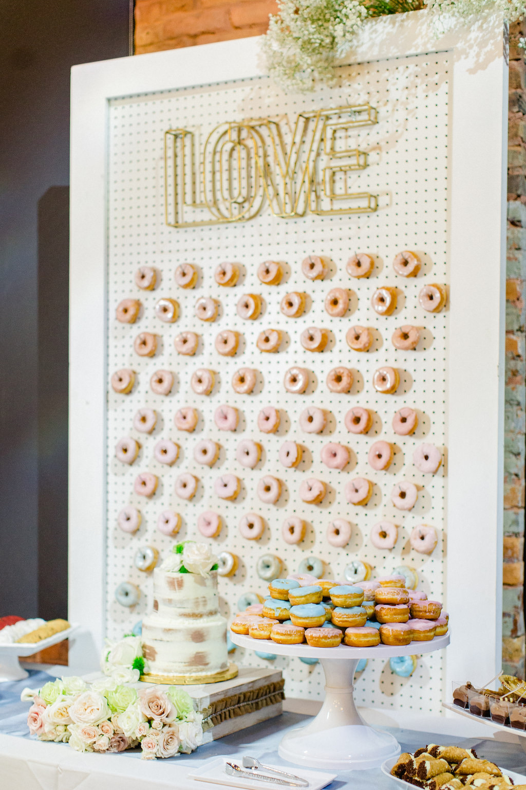 Wedding Reception Dessert Table, White Wooden Pallet Donut Wall with Gold Love Sign, White Pedestal with Donuts, Two Tier Semi Naked Wedding Cake and Blush Pink, Ivory and Greenery Floral Decor